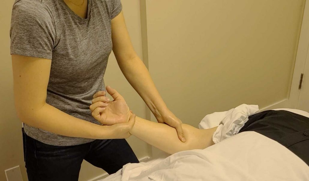 Sami Ma, RMT performing manual therapy on the patient's forearm flexor Muscles.